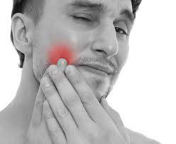 Black and white photo of man holding cheek with glowing red pain area