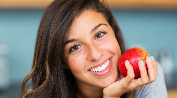 Woman Smiling with an Apple